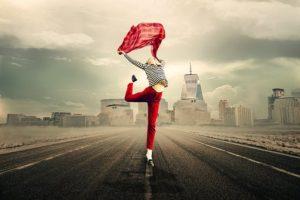 赤いパンツを履いている美脚女性が、赤いチェックのシャツをなびかせ、道で踊っている様子
