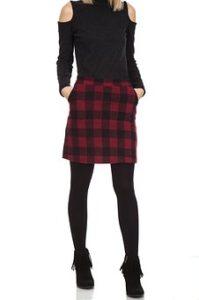 肩部分が開いているお洒落なブラックの服に、チェックのスカートと黒のタイツを合わせて履いている美脚女性の首から下の写真