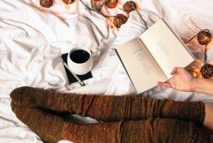 長い茶色のソックスを履いている女性の脚とコーヒーと本がベッドの上にある様子の写真