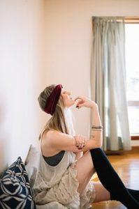 黒いソックスを履いて部屋に座り、顎に指を添えているスタイルの良い女性の写真