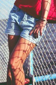 フェンスにもたれている女性の細く綺麗な太ももの写真