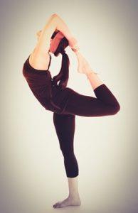 黒い着圧インナーを着てヨガ体操をしている、ポニーテール女性の写真