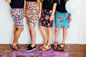 カラフルな花柄のスカートを履いている、4名の美脚女性のウエストから下の写真