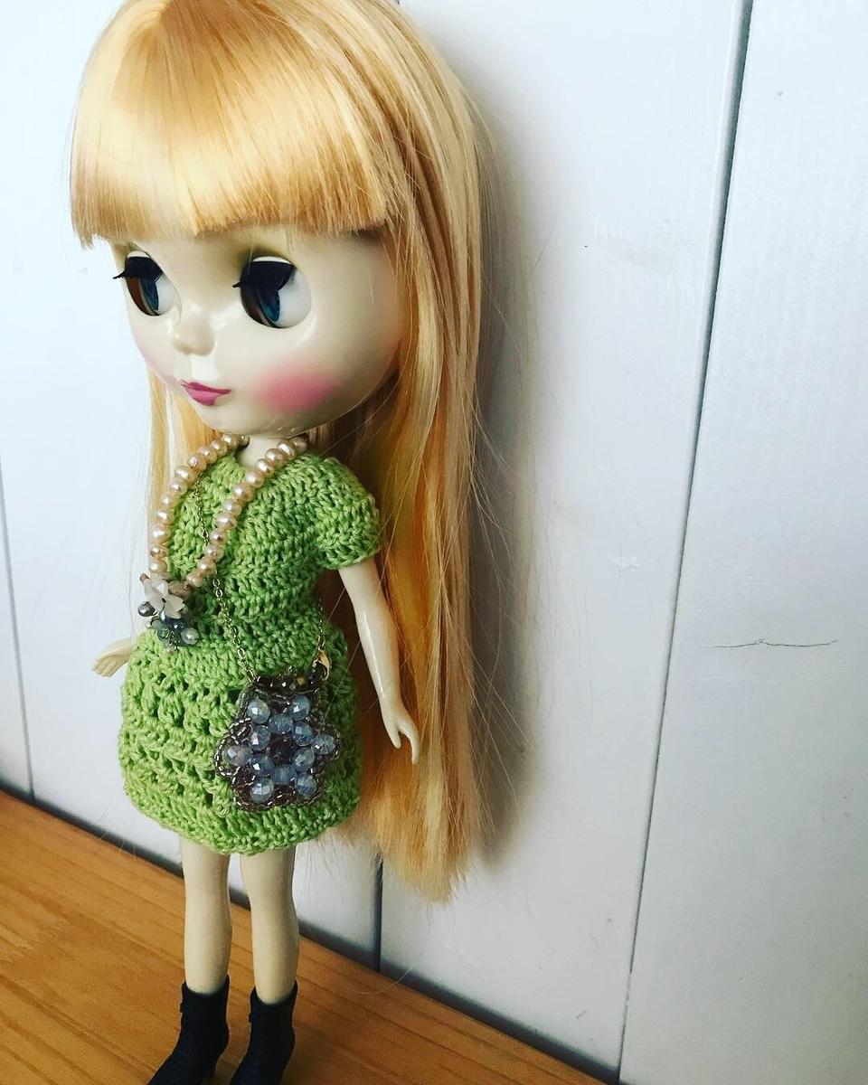 かぎ編みワンピにビーズのバッグとペンダントをつけた写真