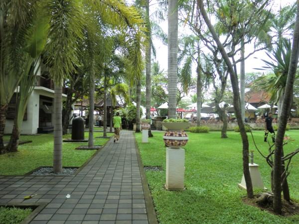 ホテルの敷地内の石畳の歩道。緑の芝生と南国の木。