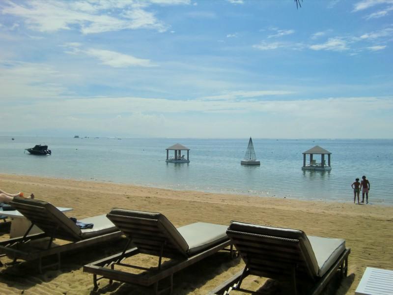 砂浜上に並ぶサンラウンジャー(長椅子)。海の中にガゼボ(東屋)が見える。