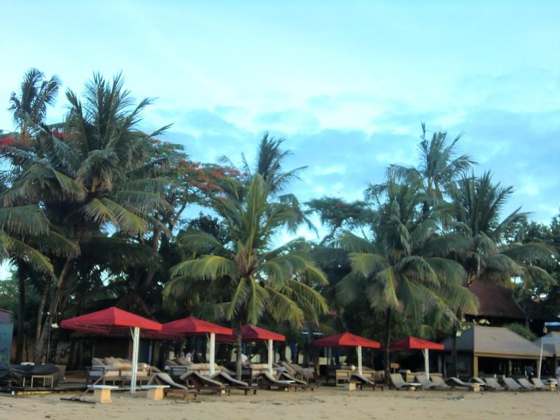 海辺、赤い屋根のテント下にデイベッドが並んでいる。背景にヤシの木。