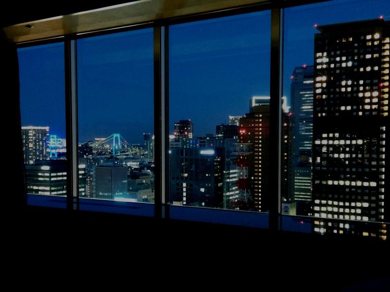 ホテルの大きな窓から望む夜景、遠くにレインボーブリッジが見える