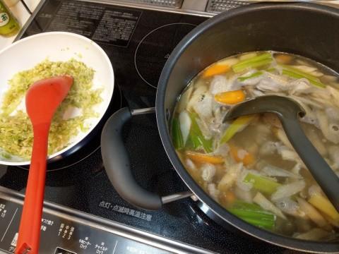 みじん切りの薬味を炒めているフライパンと、モツと野菜を煮込んでいる鍋