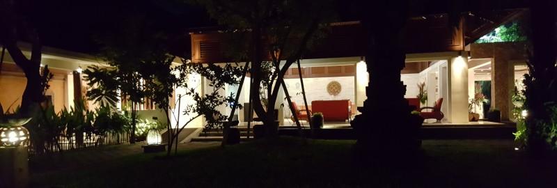 夜、バリ島のホテルの庭から明るいロビーを見る