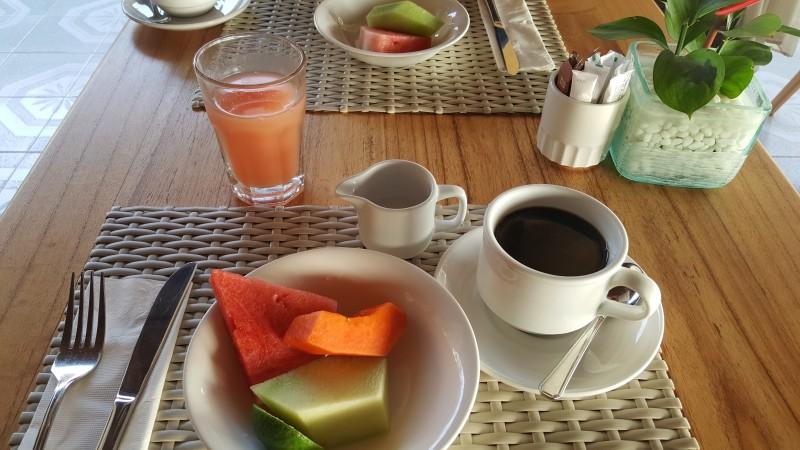 テーブルにカットフルーツを盛った皿、フルーツジュース