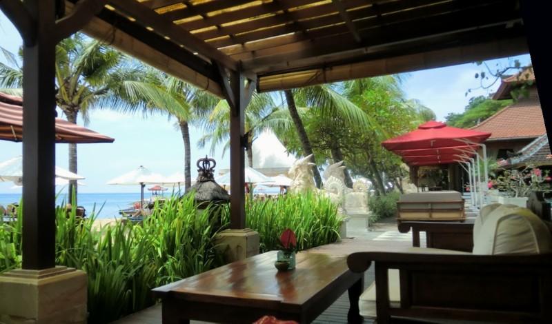 バリ島のホテルの海辺、木のローテーブルとベンチ ヤシの木も見える