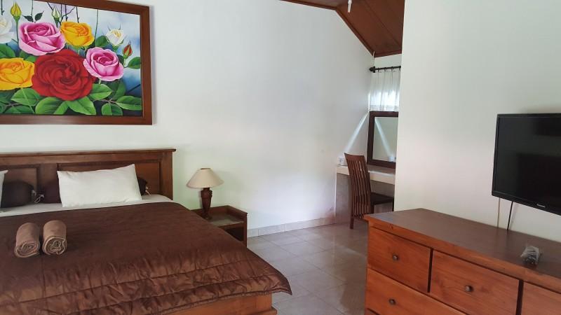 バリ島の格安ホテル 木製家具のシンプルな部屋 バラの絵が飾られている