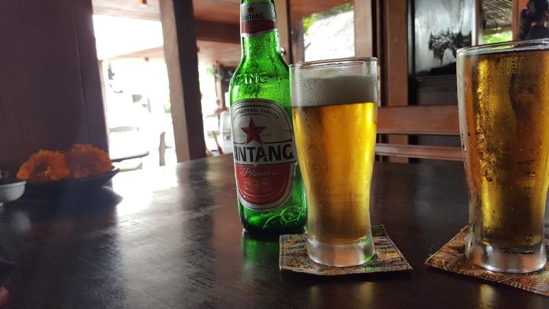 グラスに注がれたビールと、ビンタンビールの緑のビン