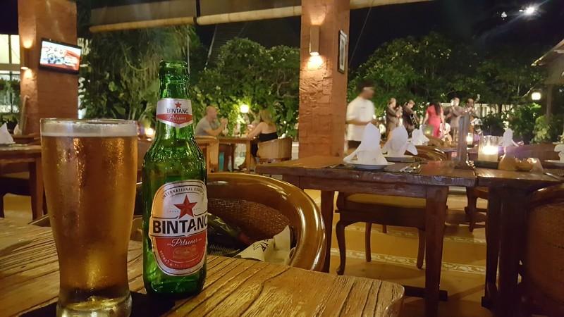 バリ島のレストラン テーブルの上にはビンタンビールの緑のビンとジョッキ