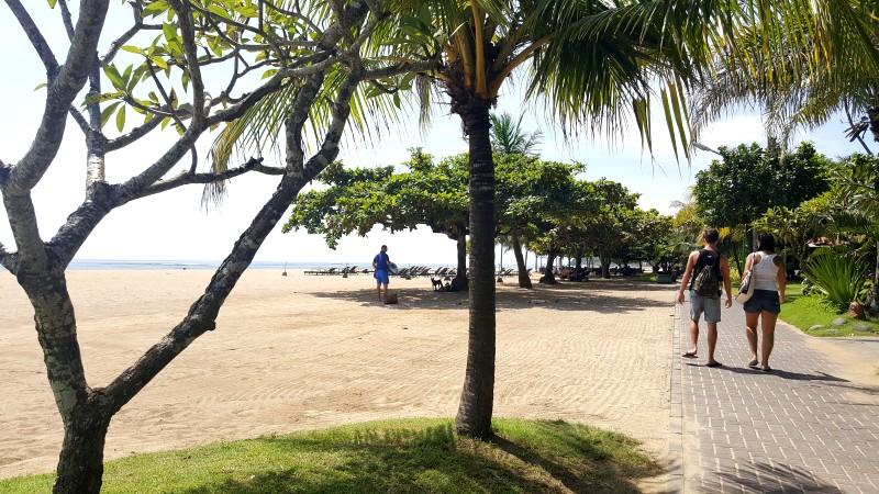 バリ島 サヌール 海岸線に沿った遊歩道 少し先の海側の砂浜にはパラソルと長椅子が並んでいる