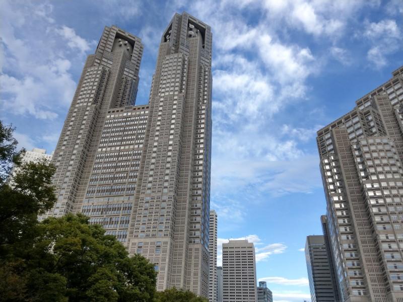 青空を背景に東京都庁庁舎を見上げる