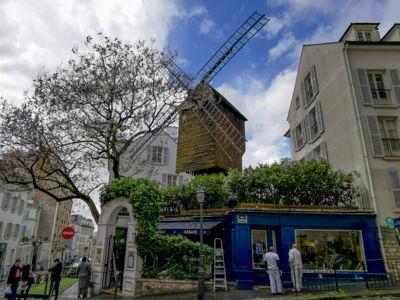 モンマルトルの丘の風車と青い外観のレストラン
