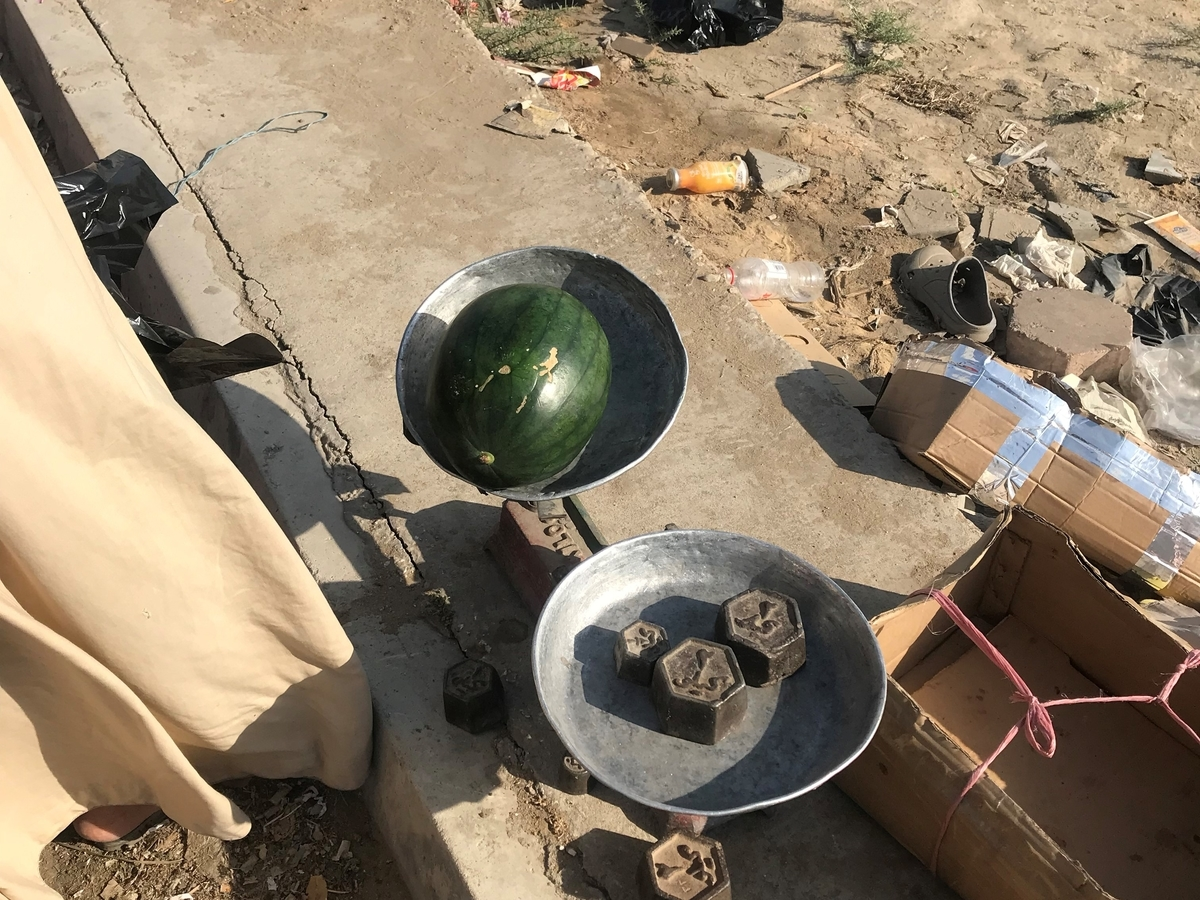 カイロ郊外の道路脇で天秤で量り売りしているフルーツ屋。格安