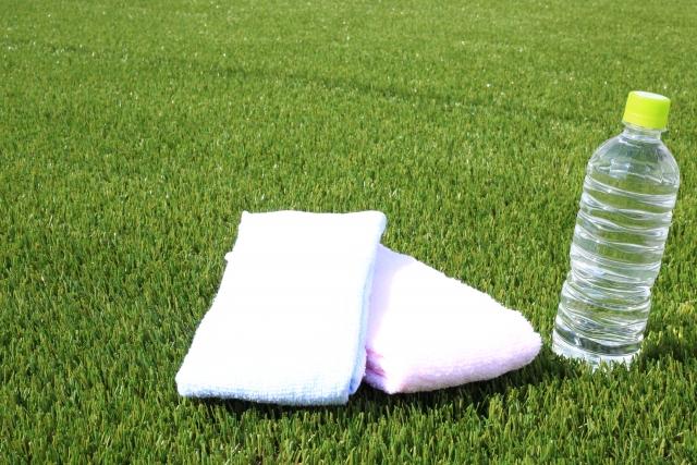 芝生の上にあるタオルと飲み物