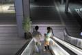 岡山市北区駅元町の風景写真 - エスカレーターの二人