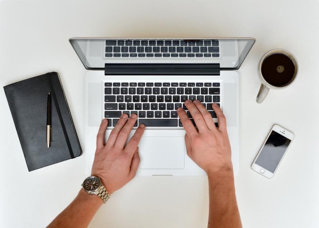 パソコンで執筆中の男性の手