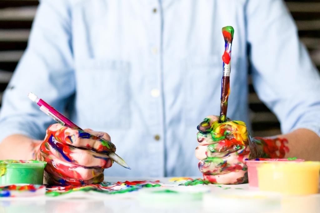 絵の具のついた筆で絵を描いている人