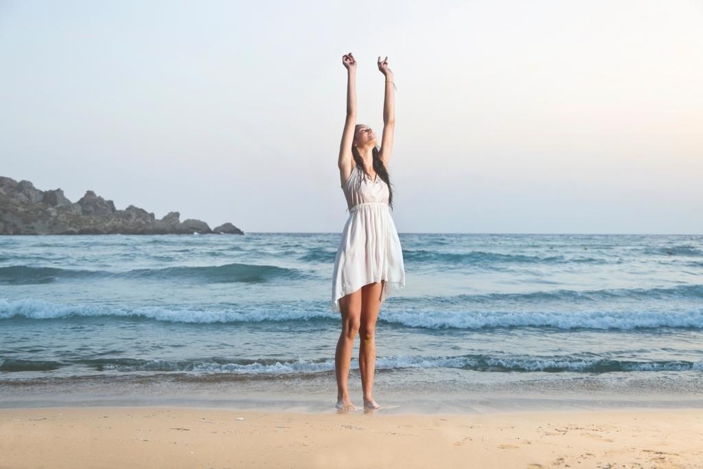 海で伸びをしている女性