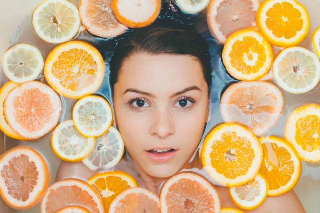 お風呂に柑橘類を浮かべて浸かっている女性