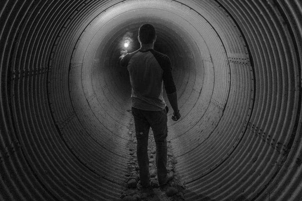 洞窟の中を懐中電灯片手に歩いている男性