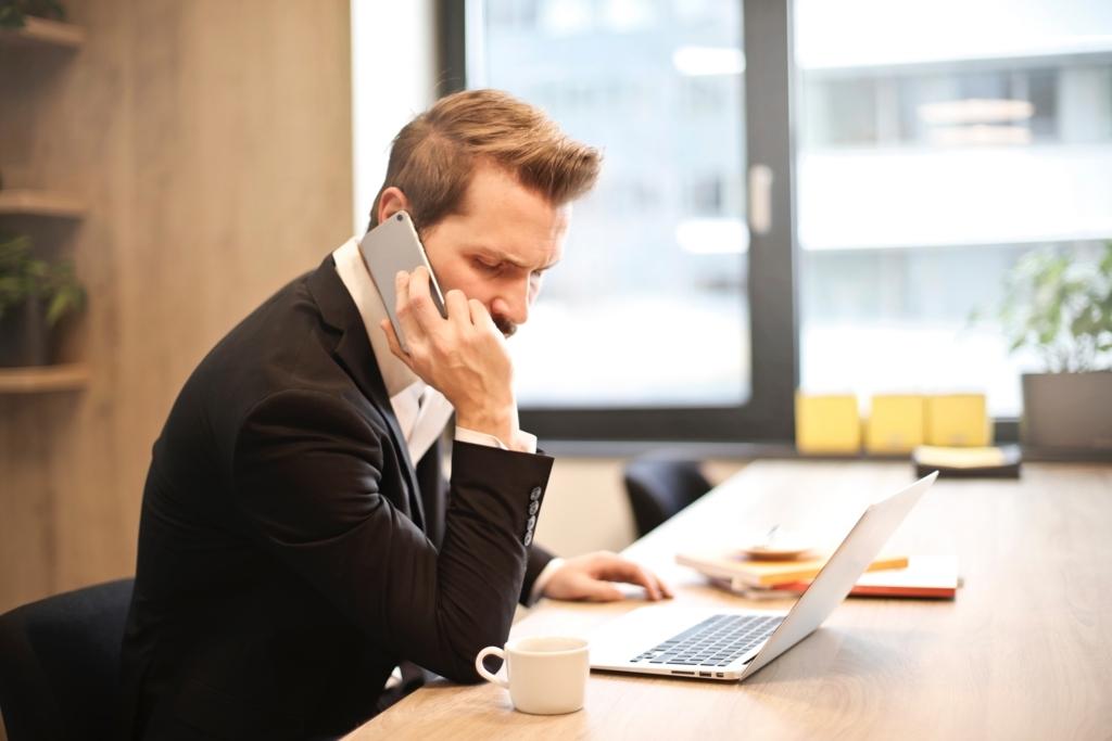 仕事をしながら電話をかけている男性