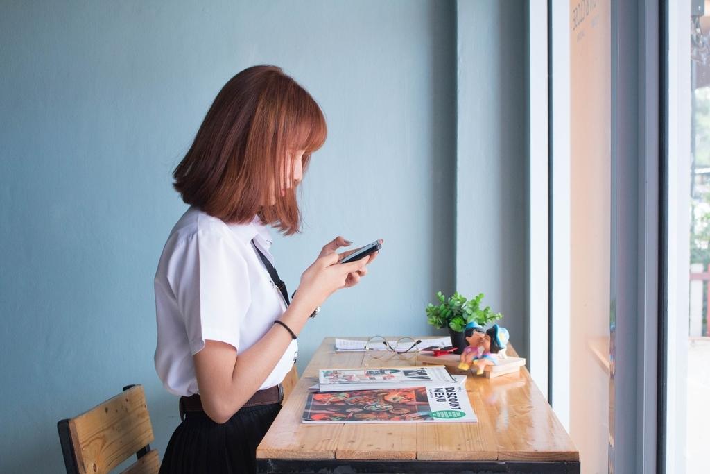 デスクで携帯を見ている女性