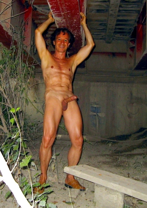 Nude shaved and erect exposed under a bridge