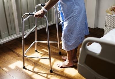 ベッドから歩行補助器具を使い立ち上がる姿