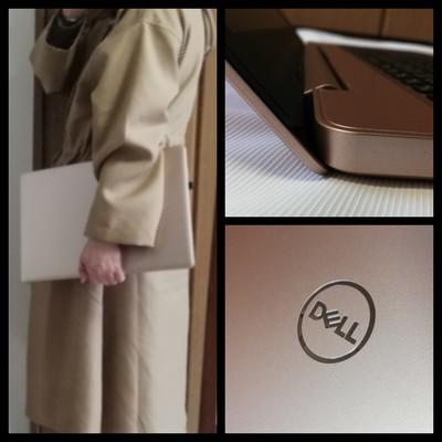 ノートパソコンを持ち立っている