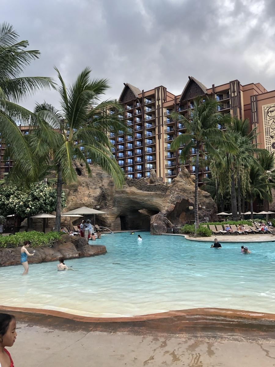 アウラニ・ディズニー・リゾートのプールからみたホテル。広いプールとヤシの木の向こうに、ディズニーらしいホテルが建っている。