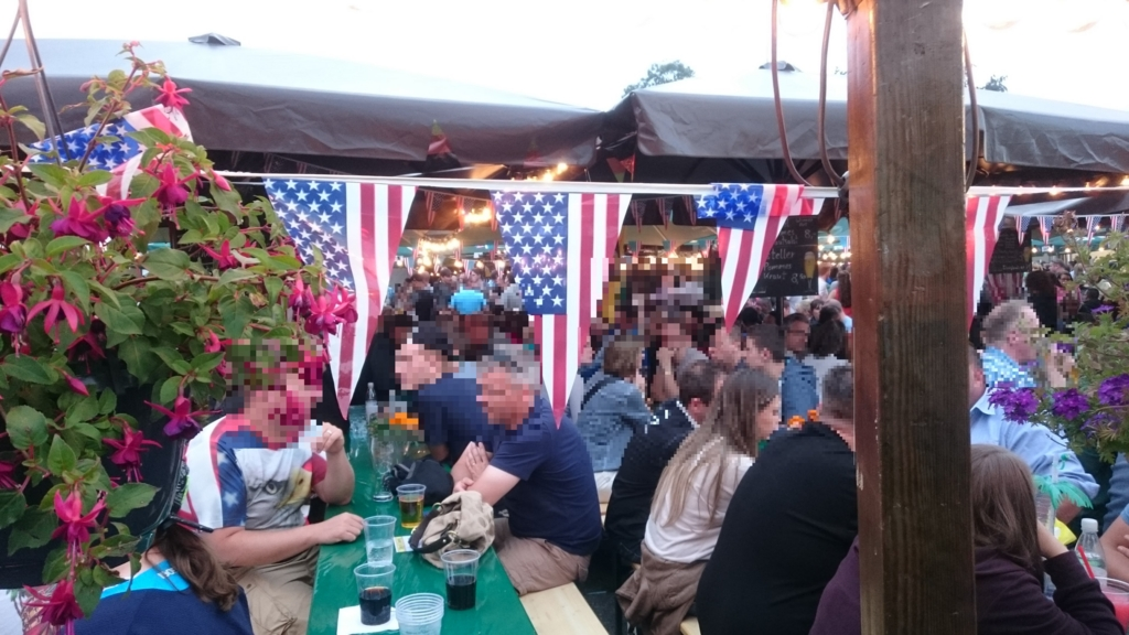 星条旗が並ぶなかでビールを飲むドイツ人