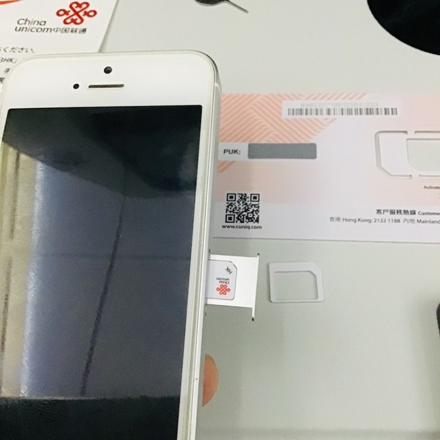 iPhoneにSIMカードを挿すところ