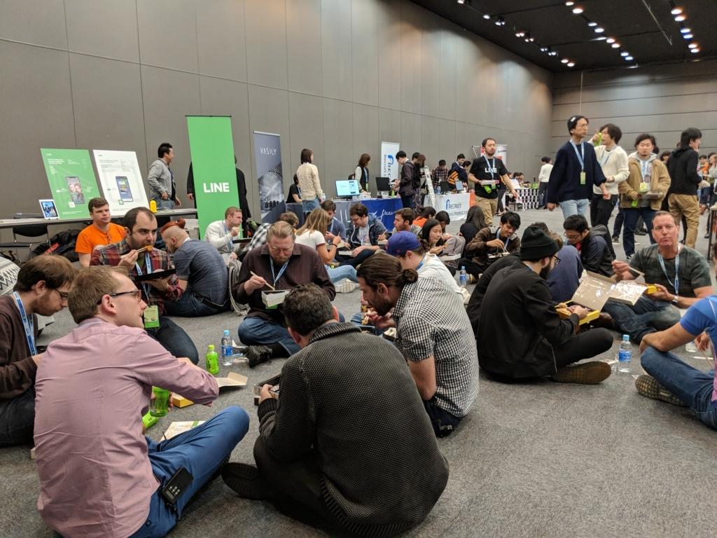 床に輪になって座りこでお弁当を食べる参加者の方々
