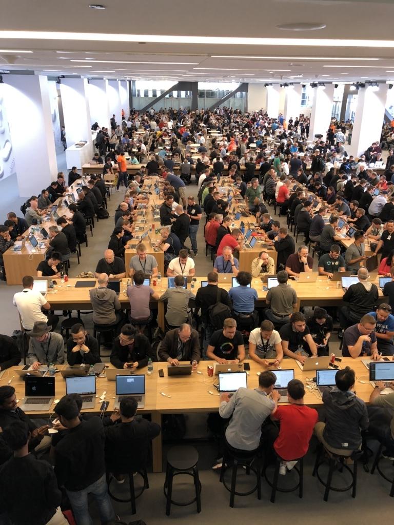 WWDC会場内の高速有線LANが使えるスペース。大きな机にたくさんの人が向かい、それぞれラップトップ(もちろんほとんどがMacBook)を開いている
