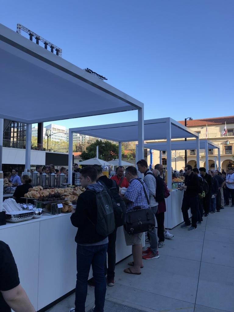 屋外のビュッフェで朝食が提供され、参加者で賑わっている