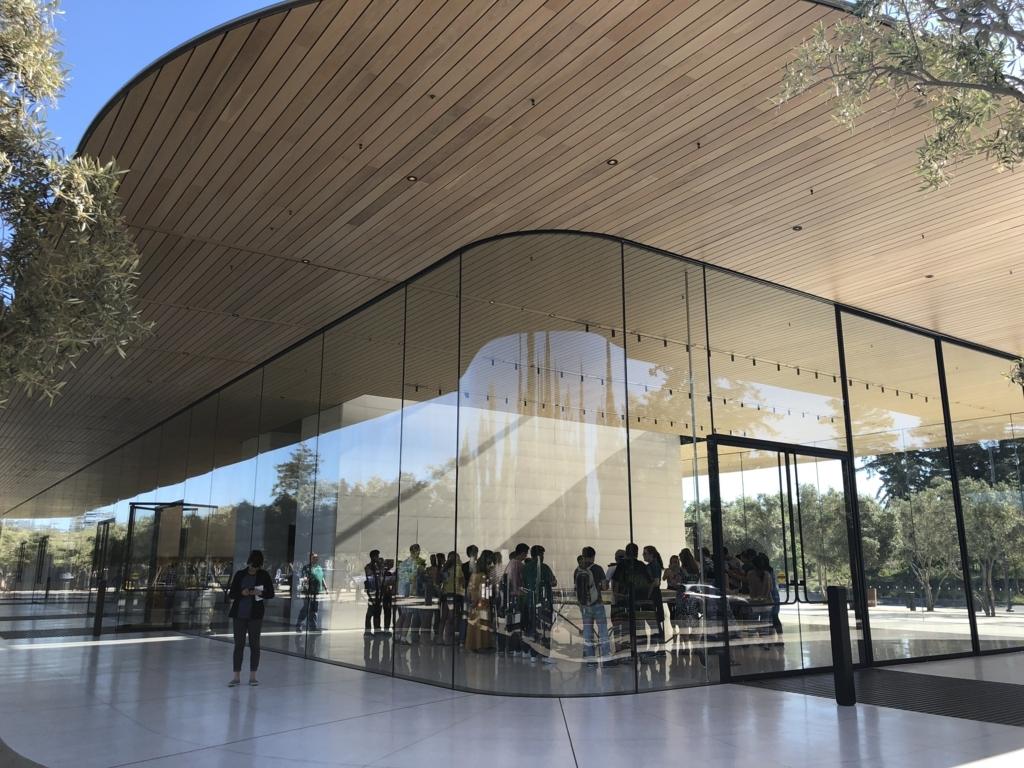 Apple Park Visitor Centerの外観。ガラスの外壁の上に屋根が載った構造