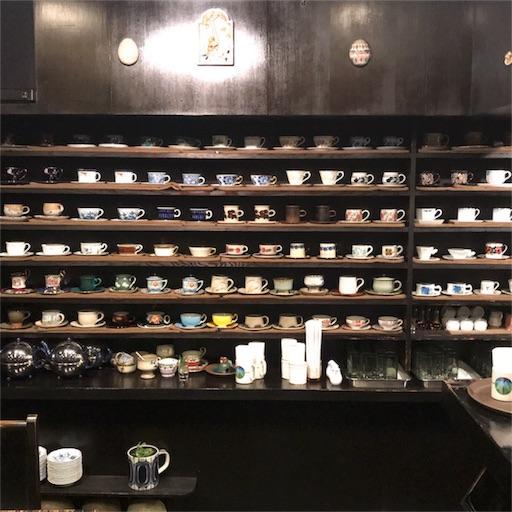 カウンター越しから眺める、整然と棚に陳列してあるコーヒーカップ