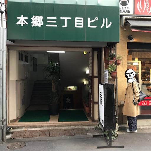 本郷三丁目の【名曲・珈琲 麦】の外観と一緒に写るM嬢