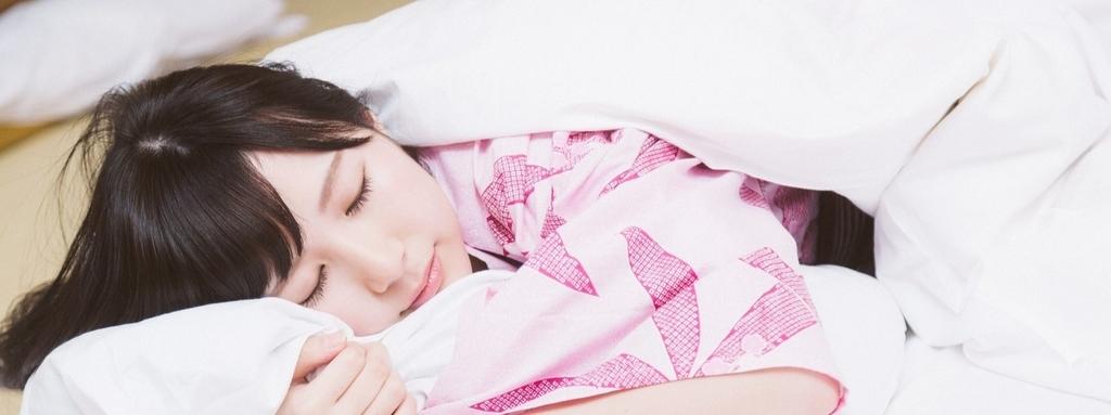 布団の中で眠る女子