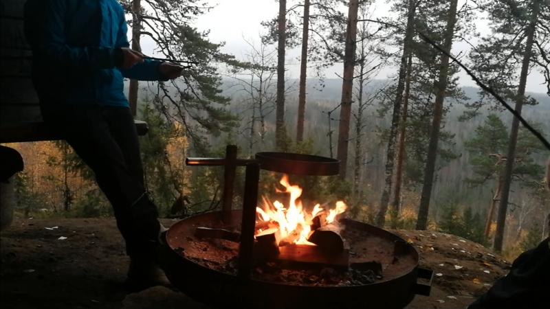 焚き火の近くでソーセージを刺す棒を作る