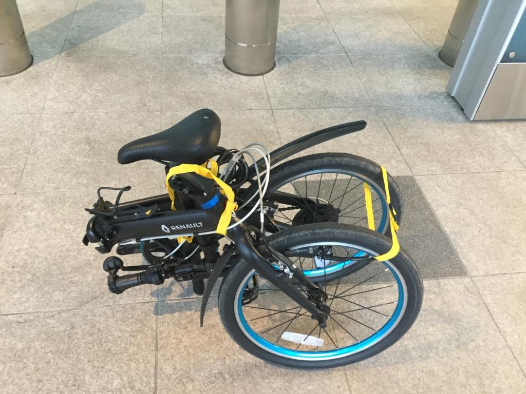 自転車を畳んで肩紐をかけた写真