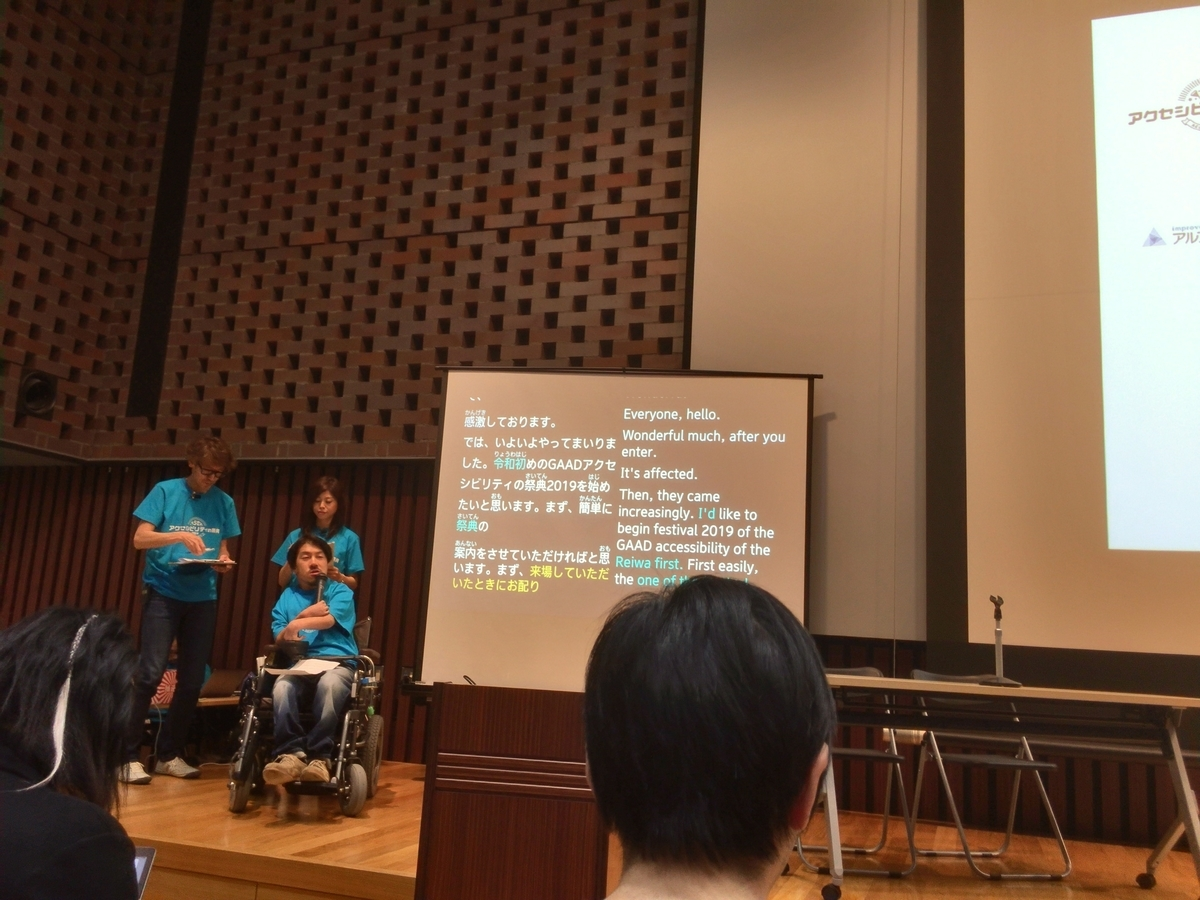 発言にあわせてUDトークを使ってリアルタイム字幕が前面スクリーンに表示されている様子