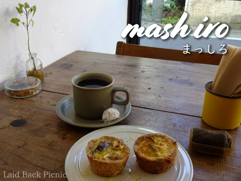 On the table, a yellow coffee cup and two small quiches