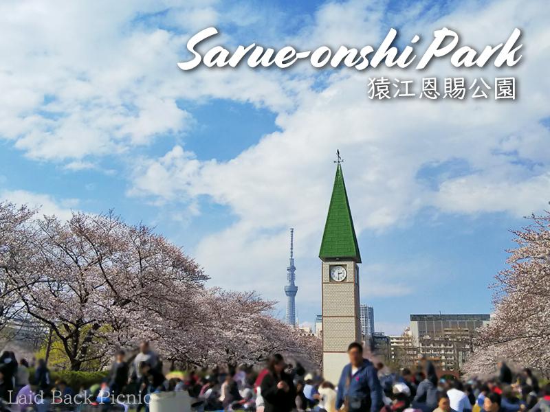 満開の桜と公園のシンボル時計塔、その向こうにスカイツリー